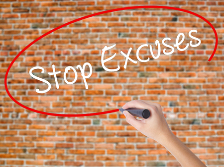 Woman Hand Writing  Stop Excuses  with black marker on visual screen. Isolated on bricks. Business concept. Stock Photo Stock Photo