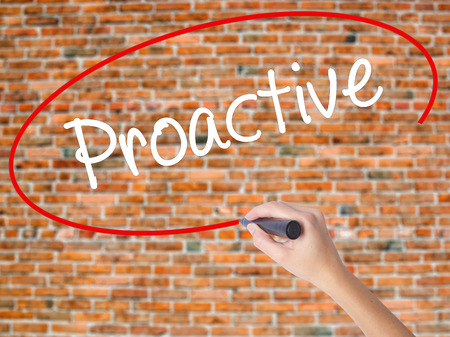 Woman Hand Writing Proactive with black marker on visual screen. Isolated on bricks. Business concept. Stock Photo