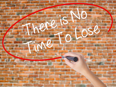 Woman Hand Writing There is No Time To Lose with black marker on visual screen. Isolated on bricks. Business concept. Stock Photo Stock Photo