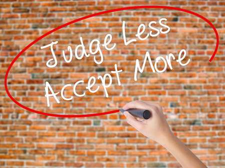 Woman Hand Writing Judge Less Accept More with black marker on visual screen. Isolated on bricks. Business concept. Stock Photo Stock Photo