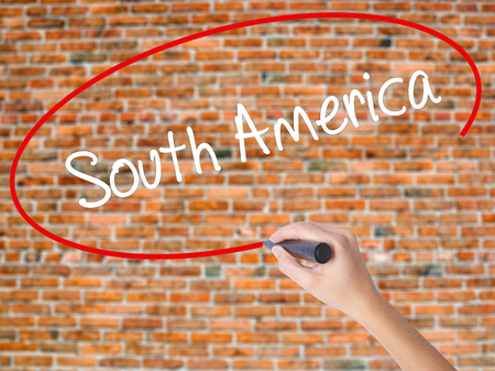 Woman Hand Writing South America with black marker on visual screen. Isolated on bricks. Business concept. Stock Photo Foto de archivo