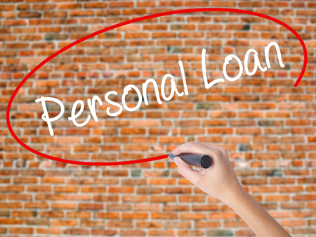 Woman Hand Writing Personal Loan with black marker on visual screen. Isolated on bricks. Business concept. Stock Photo
