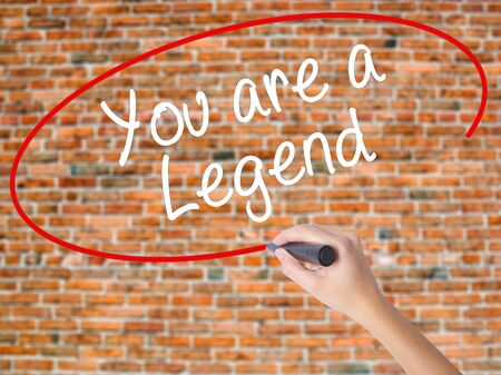 triumphant: Woman Hand Writing You are a Legend   with black marker on visual screen. Isolated on bricks. Business concept. Stock Photo