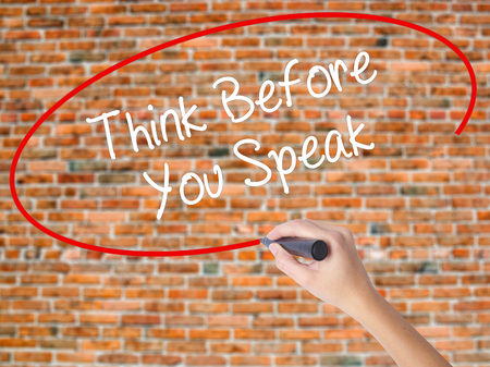 Woman Hand Writing Think Before You Speak with black marker on visual screen. Isolated on bricks. Business concept. Stock Photo Stock Photo