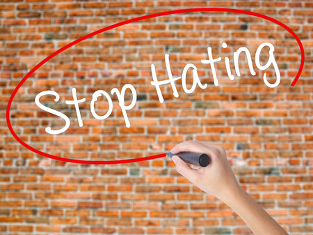 venganza: Woman Hand Writing Stop Hating  with black marker on visual screen. Isolated on bricks. Business concept. Stock Photo