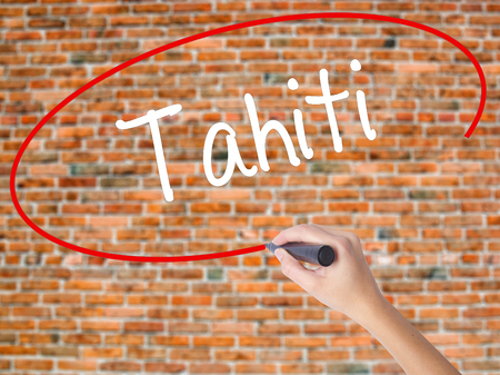 tahitian: Woman Hand Writing Tahiti with black marker on visual screen. Isolated on bricks. Business concept. Stock Photo