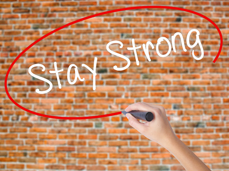 trouble free: Woman Hand Writing Stay Strong with black marker on visual screen. Isolated on bricks. Business concept. Stock Photo