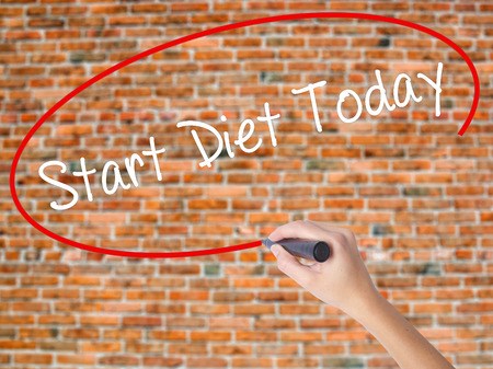 Woman Hand Writing Start Diet Today  with black marker on visual screen. Isolated on bricks. Business concept. Stock Photo
