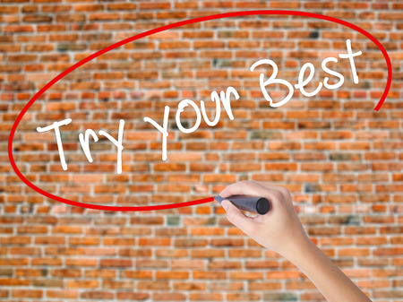 Woman Hand Writing Try your Best with black marker on visual screen. Isolated on bricks. Business, technology, internet concept. Stock  Photo