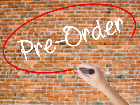 preorder: Woman Hand Writing Pre-Order  with black marker on visual screen. Isolated on bricks. Business concept. Stock Photo