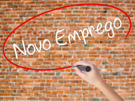 Woman Hand Writing  Novo Emprego (New Job in Portuguese)   with black marker on visual screen. Isolated on bricks. Business concept. Stock Photo