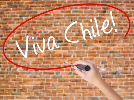 Mujer escribiendo a mano Viva Chile! con marcador negro en la pantalla visual. Aislado en ladrillos. Concepto de negocio. Foto de stock
