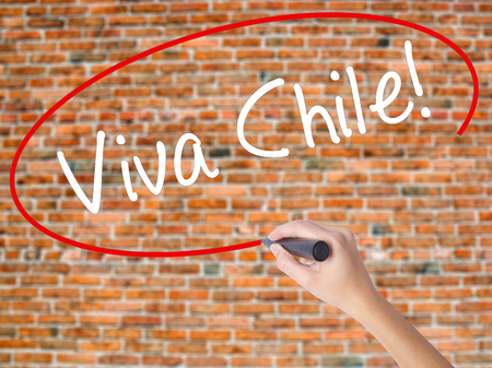 bandera chilena: Woman Hand Writing Viva Chile! with black marker on visual screen. Isolated on bricks. Business concept. Stock Photo