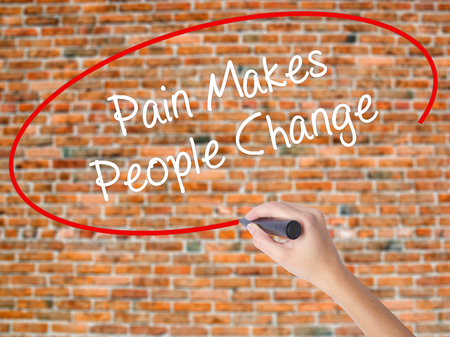 Woman Hand Writing Pain Makes People Change  with black marker on visual screen. Isolated on bricks. Business, technology, internet concept. Stock Photo