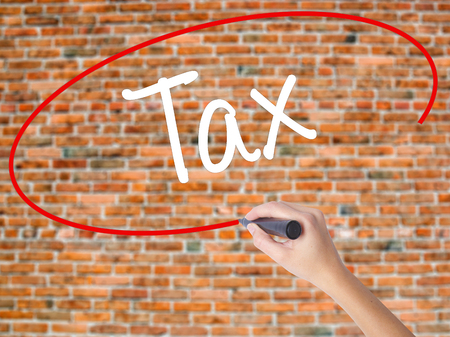 Woman Hand Writing Tax with black marker on visual screen. Isolated on bricks. Business concept. Stock Photo Stock Photo