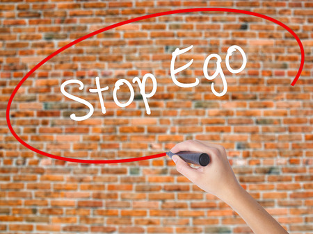 Woman Hand Writing  Stop Ego with black marker on visual screen. Isolated on bricks. Business concept. Stock Photo