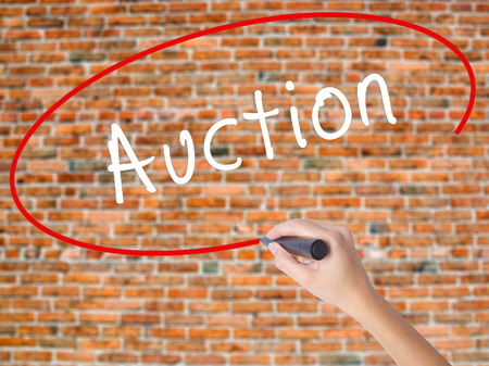 Woman Hand Writing Auction with black marker on visual screen. Isolated on bricks. Business concept. Stock Photo