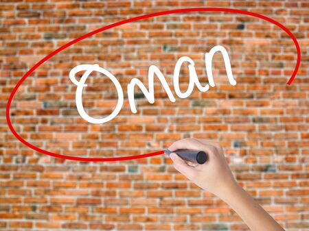 Woman Hand Writing Oman   with black marker on visual screen. Isolated on bricks. Business concept. Stock Photo Stock Photo