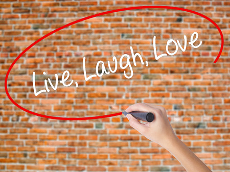 Woman Hand Writing Live Laugh Love with black marker on visual screen. Isolated on bricks. Business concept. Stock Photo