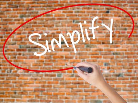 istruzione: Scrittura a mano della donna Semplificare con pennarello nero su schermo visivo. Isolato su mattoni Concetto di business Foto d'archivio