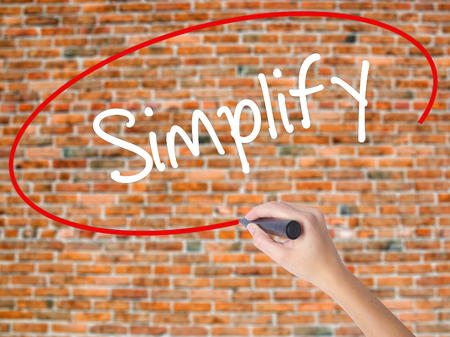 Woman Hand Writing Simplify with black marker on visual screen. Isolated on bricks. Business concept. Stock Photo Stock Photo