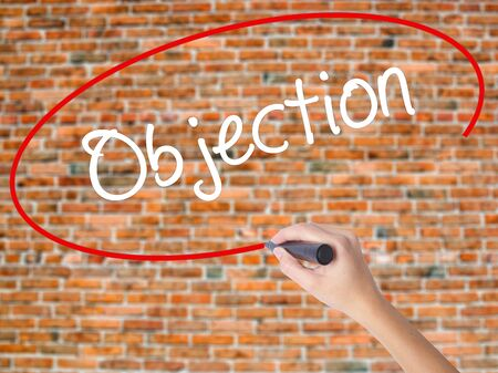 Woman Hand Writing Objection with black marker on visual screen. Isolated on bricks. Business concept. Stock Photo