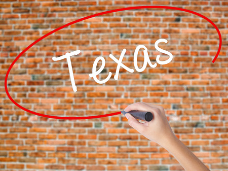Woman Hand Writing Texas  with black marker on visual screen. Isolated on bricks. Business, technology, internet concept. Stock Photo