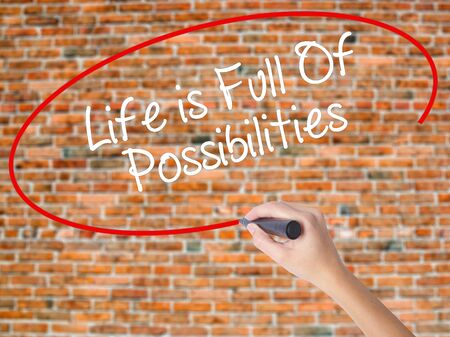Woman Hand Writing Life is Full Of Possibilities with black marker on visual screen. Isolated on bricks. Business concept. Stock Photo Stock Photo