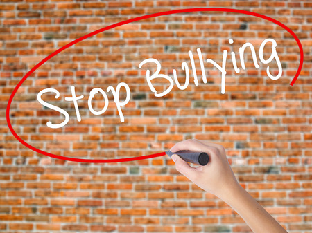 Woman Hand Writing Stop Bullying with black marker on visual screen. Isolated on bricks. Business concept. Stock Photo