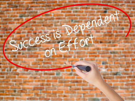 advise: Woman Hand Writing Success is Dependent on Effort with black marker on visual screen. Isolated on bricks. Business concept. Stock Photo Stock Photo