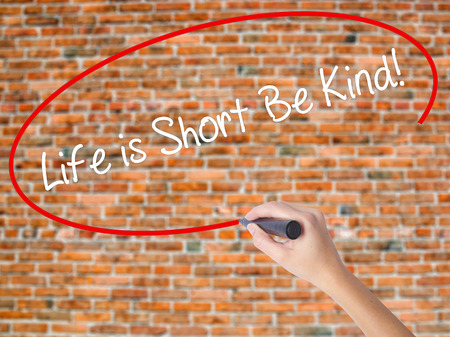 Woman Hand Writing Life is Short Be Kind! with black marker on visual screen. Isolated on bricks. Business concept. Stock Photo