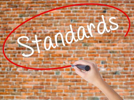 Vrouw Hand schrijven normen met zwarte marker op visuele scherm. Geïsoleerd op bakstenen. Bedrijfsconcept. Stock foto Stockfoto - 71605597