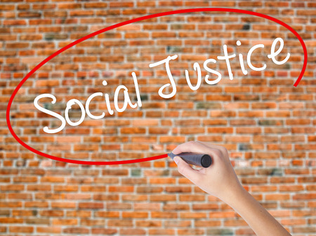 Woman Hand Writing Social Justice with black marker on visual screen. Isolated on bricks. Business concept. Stock Photo