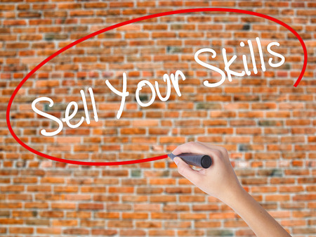 Woman Hand Writing Sell Your Skills with black marker on visual screen. Isolated on bricks. Business concept. Stock Photo