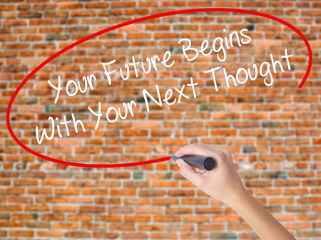 Woman Hand Writing Your Future Begins With Your Next Thought with black marker on visual screen. Isolated on bricks. Business concept. Stock Photo Stock Photo
