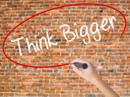 Woman Hand Writing Think Bigger with black marker on visual screen. Isolated on bricks. Business, technology, internet concept. Stock  Photo