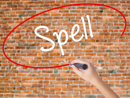 Woman Hand Writing Spell with black marker on visual screen. Isolated on bricks. Business concept. Stock Photo