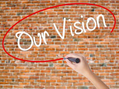 Woman Hand Writing Our Vision with black marker on visual screen. Isolated on bricks. Business concept. Stock Photo