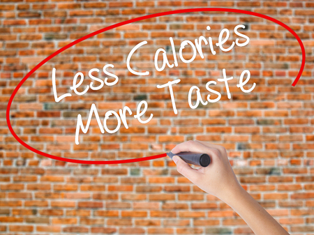 Woman Hand Writing Less Calories More Taste with black marker on visual screen. Isolated on bricks. Business concept. Stock Photo