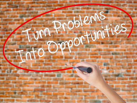 Woman Hand Writing Turn Problems into Opportunities with black marker on visual screen. Isolated on bricks. Business concept. Stock Photo