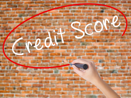 Woman Hand Writing Credit Score black marker on visual screen. Isolated on bricks. Business concept. Stock Photo