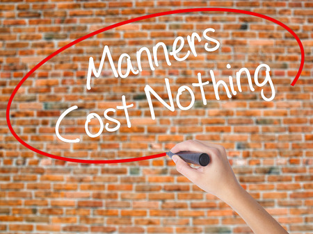 manners: Woman Hand Writing Manners Cost Nothing with black marker on visual screen. Isolated on bricks. Business concept. Stock Photo