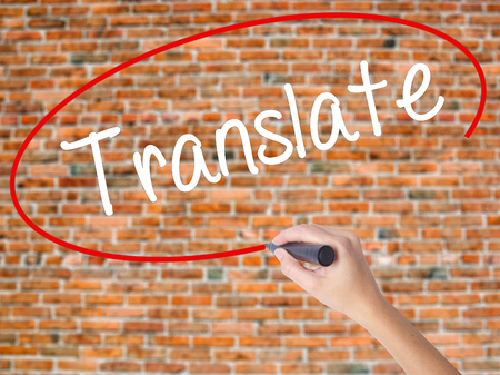 Woman Hand Writing Translate with black marker on visual screen. Isolated on bricks. Business concept. Stock Photo