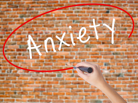 Woman Hand Writing Anxiety with black marker on visual screen. Isolated on bricks. Business concept. Stock Photo