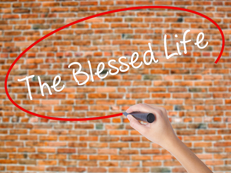 Woman Hand Writing The Blessed Life  with black marker on visual screen. Isolated on bricks. Business concept. Stock Photo