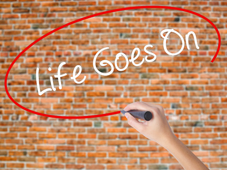 Woman Hand Writing Life Goes On with black marker on visual screen. Isolated on bricks. Business concept. Stock Photo
