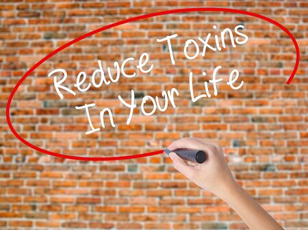 Woman Hand Writing Reduce Toxins In Your Life with black marker on visual screen. Isolated on bricks. Business concept. Stock Photo Stock Photo
