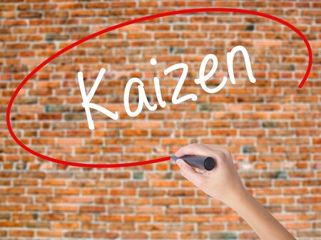 Woman Hand Writing Kaizen with black marker on visual screen. Isolated on bricks. Business concept. Stock Photo