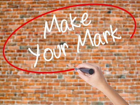 realize: Woman Hand Writing Make Your Mark with black marker on visual screen. Isolated on bricks. Business concept. Stock Photo