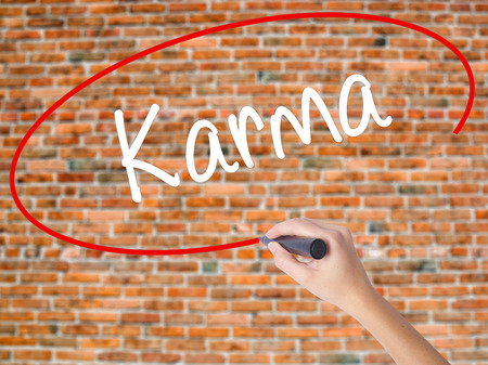 Woman Hand Writing Karma  with black marker on visual screen. Isolated on bricks. Business concept. Stock Photo